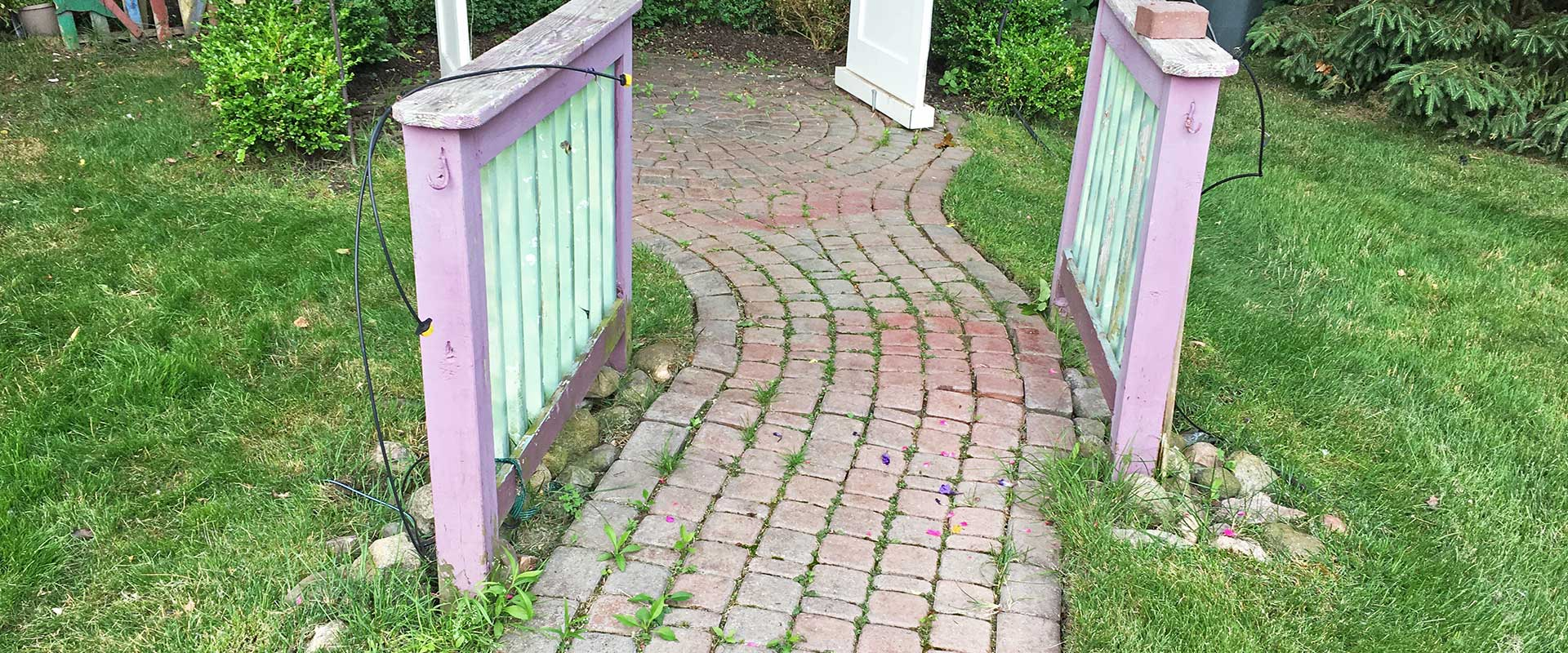 un-leveled brick paver walkway with weeds and moss growing through the joints